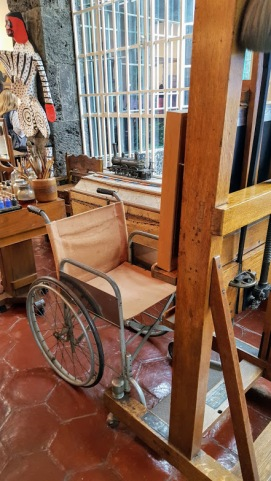 Frida's wheelchair in front of her easel.